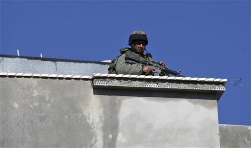 An Israeli border police officer guards a rooftop in the West Bank village of Awarta, after five people were killed in the nearby Jewish settlement of Itamar Saturday, March 12, 2011. A Palestinian infiltrated Itamar early Saturday and killed five people, the Israeli military said. Israeli media is reporting that the dead are all members of the same family with parents and three children aged 11, 3 and an infant, all reported to have been stabbed while they slept. (AP Photo/Nasser Ishtayeh)