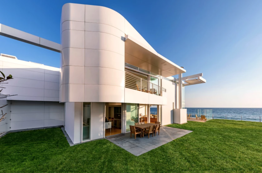 A modern home with aluminum panels has a rectangular patio and deep green lawn.