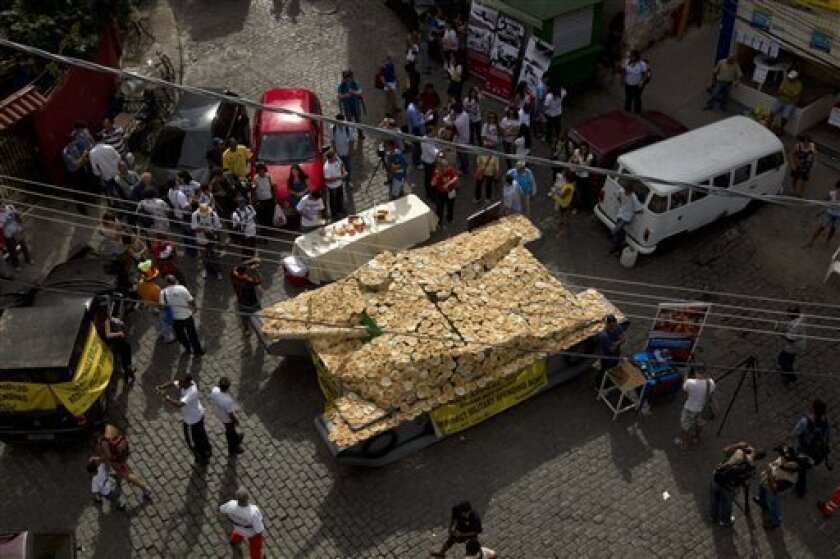 "A fake life-sized war tank covered by bread sits on display in the Santa Marta slum as part of a ""Bread not Bombs"" protest on the sidelines of the Rio+20 UN Conference on Sustainable Development in Rio de Janeiro, Brazil, Tuesday, June 19, 2012. Activists placed the fake war tank covered with bread"