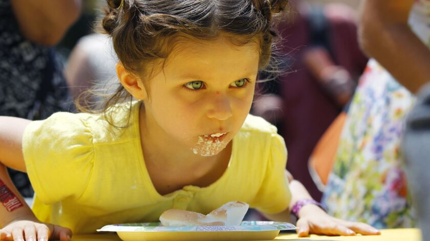Luna Larkin, 4, of Chula Vista keeps an eye on the competition during a lemon pie eating contest during the 20th annual Lemon Festival in Chula Vista in 2016.