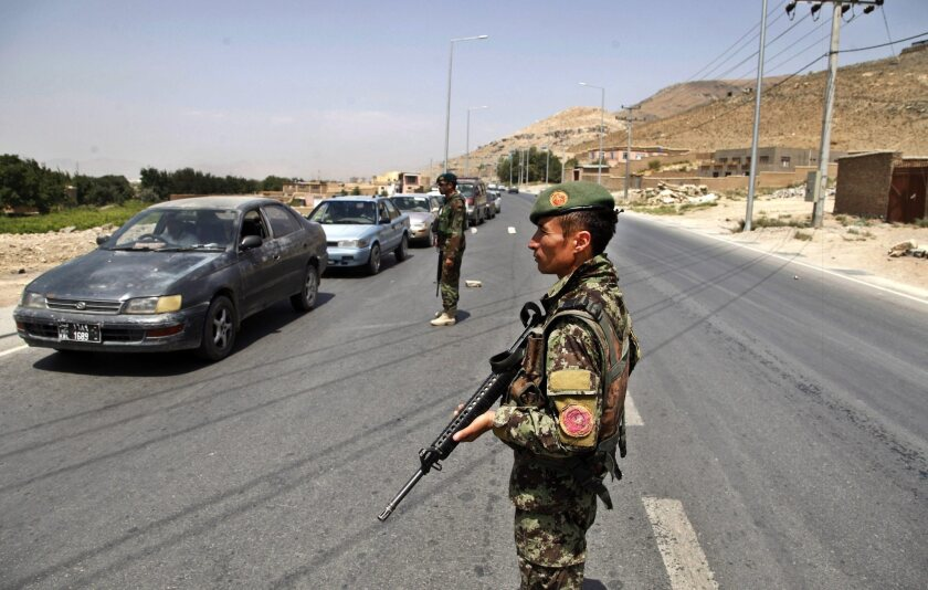 Members of the Afghan security forces stand guard on a Kabul roadside on July 29 as security is increased following reports of the death of Mullah Mohammad Omar, the leader of the Afghan Taliban.