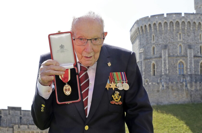 Tom Moore holds his medal up after being knighted by Queen Elizabeth II