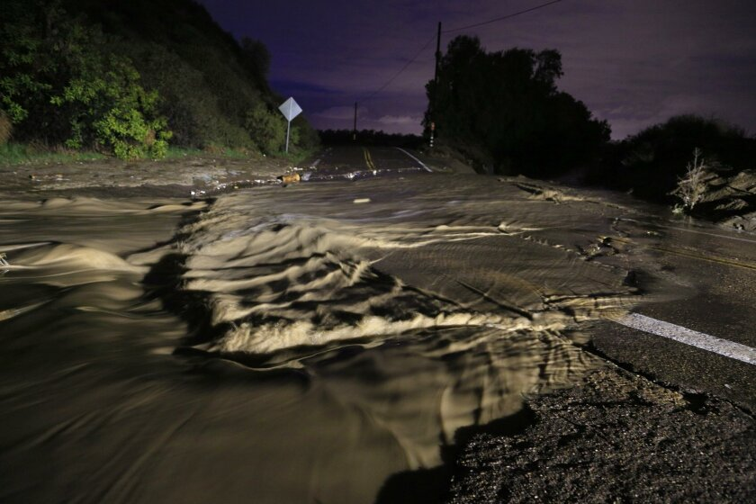 Rain water floods Monument Road near the Tijuana River Valley.