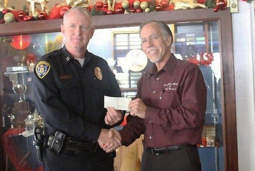 SDPD Captain Brian Ahearn (left) receives a check for $1,000 toward renovations to the police storefront from Mission Bay Real Estate Association President Mike Lawson. Courtesy