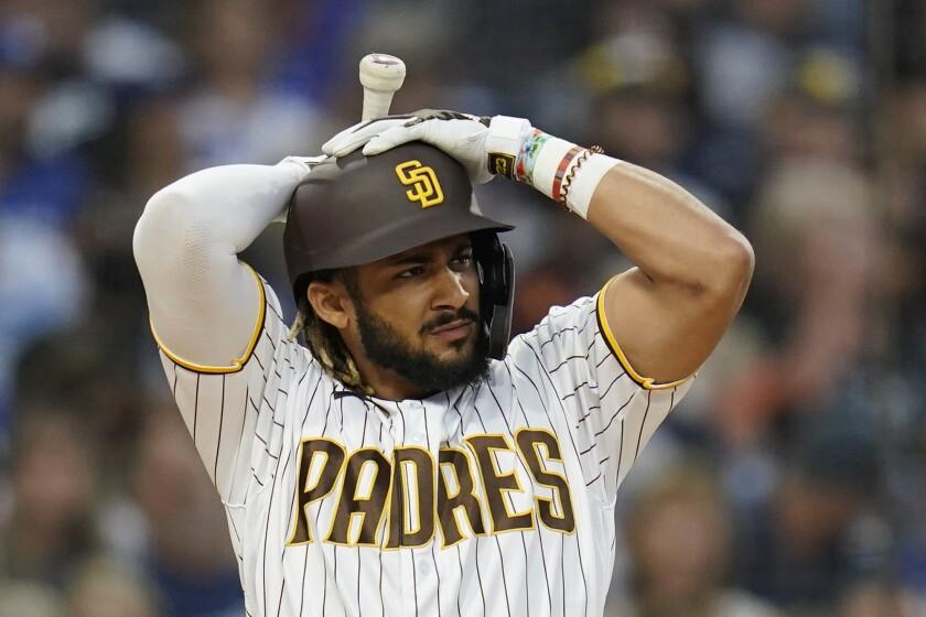 San Diego Padres' Fernando Tatis Jr. adjusts his helmet before striking out.