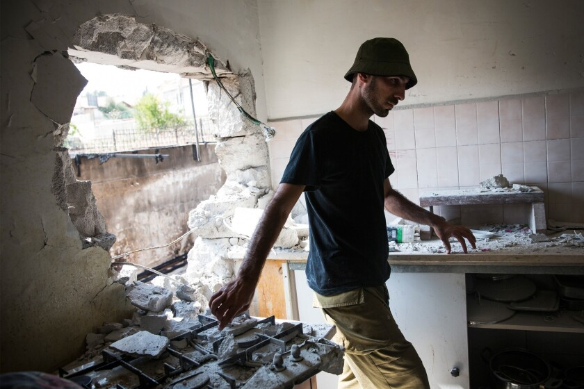 An Israeli soldier inspects an Israeli home allegedly hit by a Hamas rocket in Sderot, Israel.