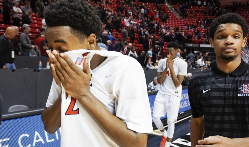 The Aztecs' Jeremy Hemsley, left, and Dakarai Allen, background center, walk off the court after the Aztecs lost to Grand Canyon 52-45.