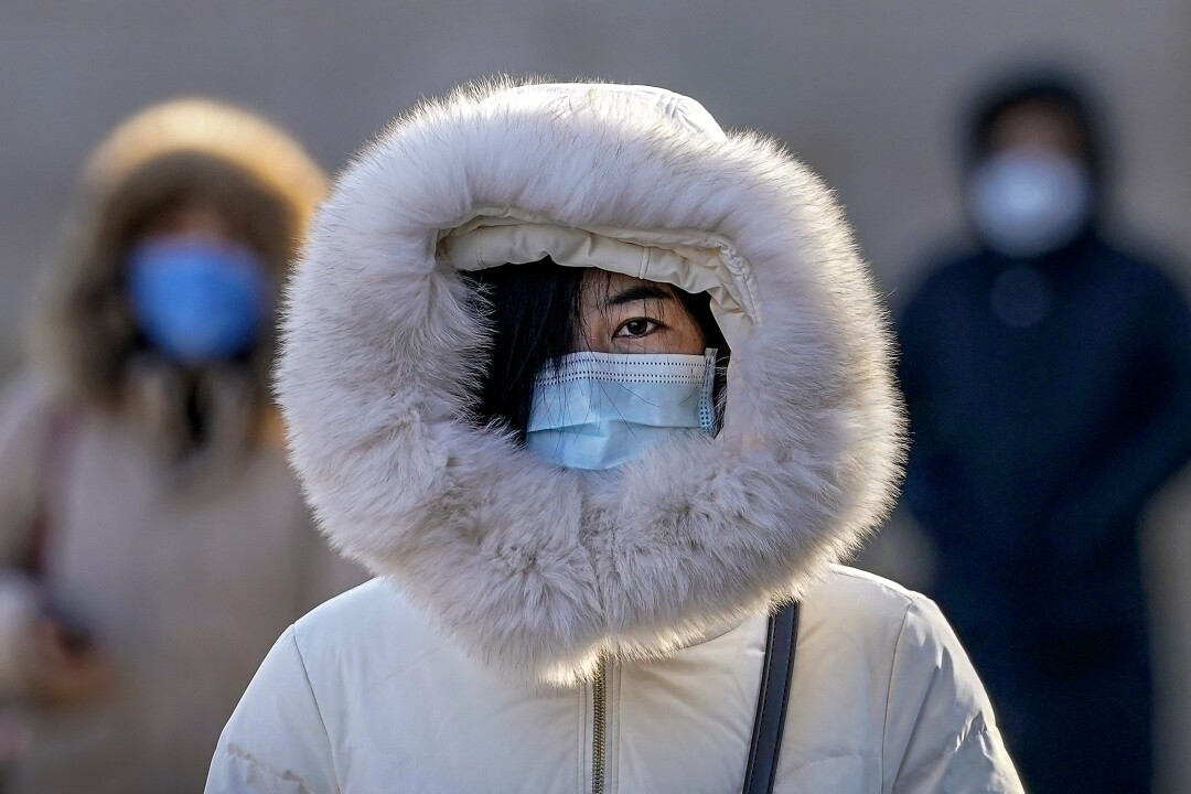 A pedestrian in Beijing relies on a mask and a hood to ward off coronavirus contagion and the chill.