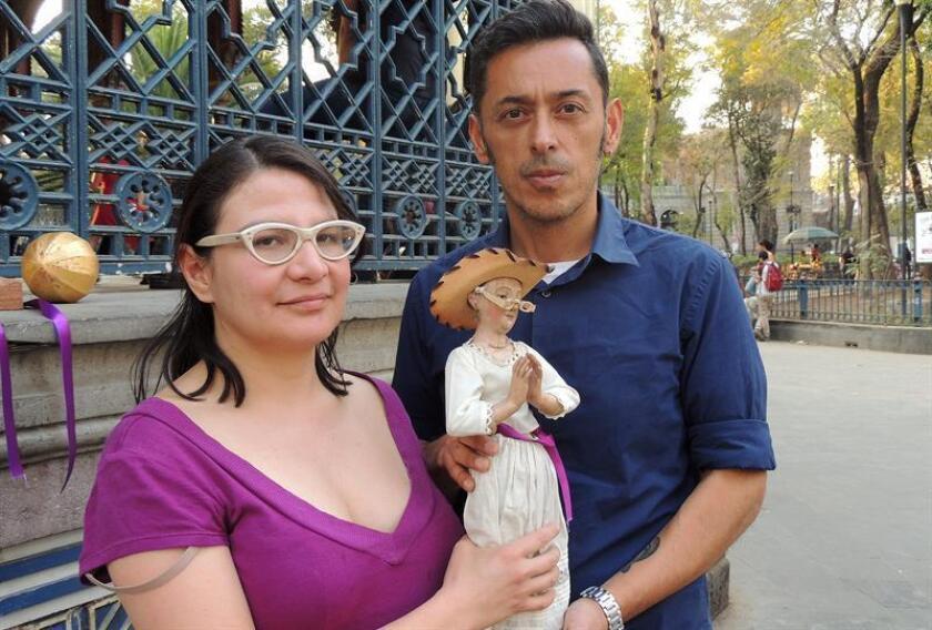 Los vecinos de los barrios de Santa María la Rivera y Juárez, Sandra Valenzuela (i) y Jorge Baca sostienen una imagen de Santa María La Juarica en un parque en Ciudad de México (México) este 8 de enero de 2018. EFE
