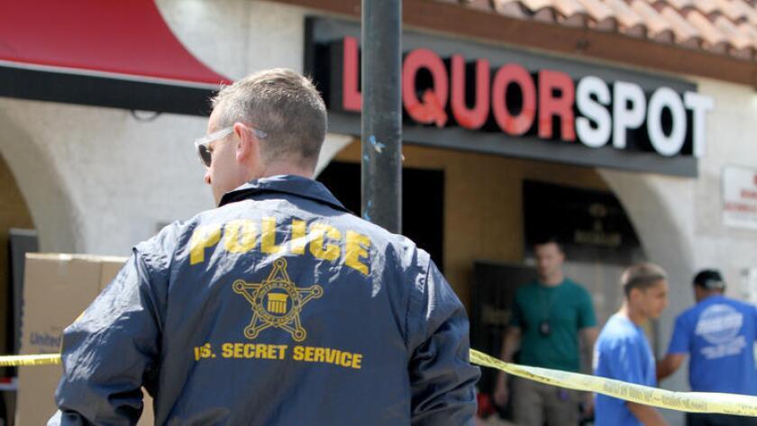La policía del Servicio Secreto de Estados Unidos remueve mercancía de una licorería en la cuadra 300 de North Verdugo Boulevard. (Raul Roa / Glendale News-Press)