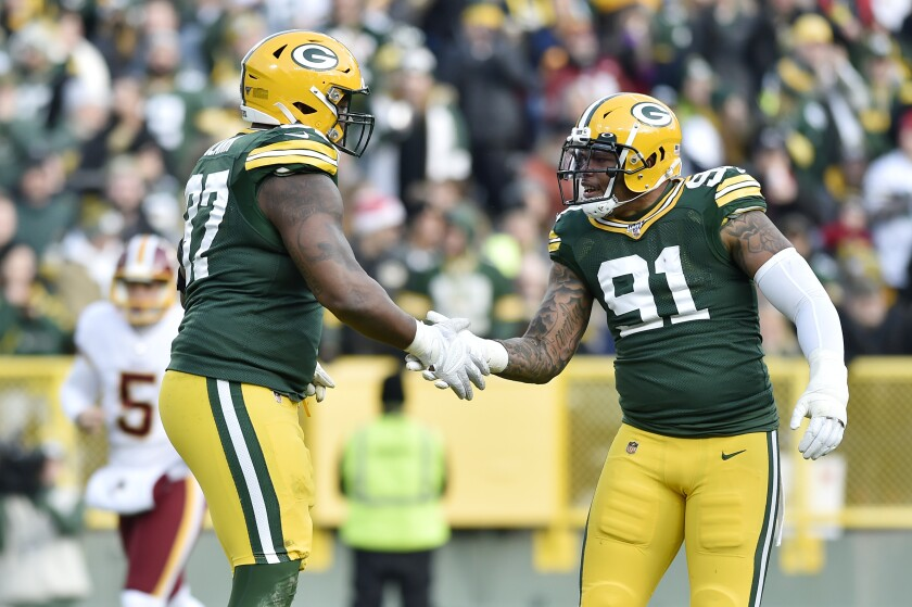 Green Bay Packers' Preston Smith (91) congratulates teammate Kenny Clark (97) for his sack in the second half against the Washington Redskins on Dec. 8 in Green Bay, Wisc.