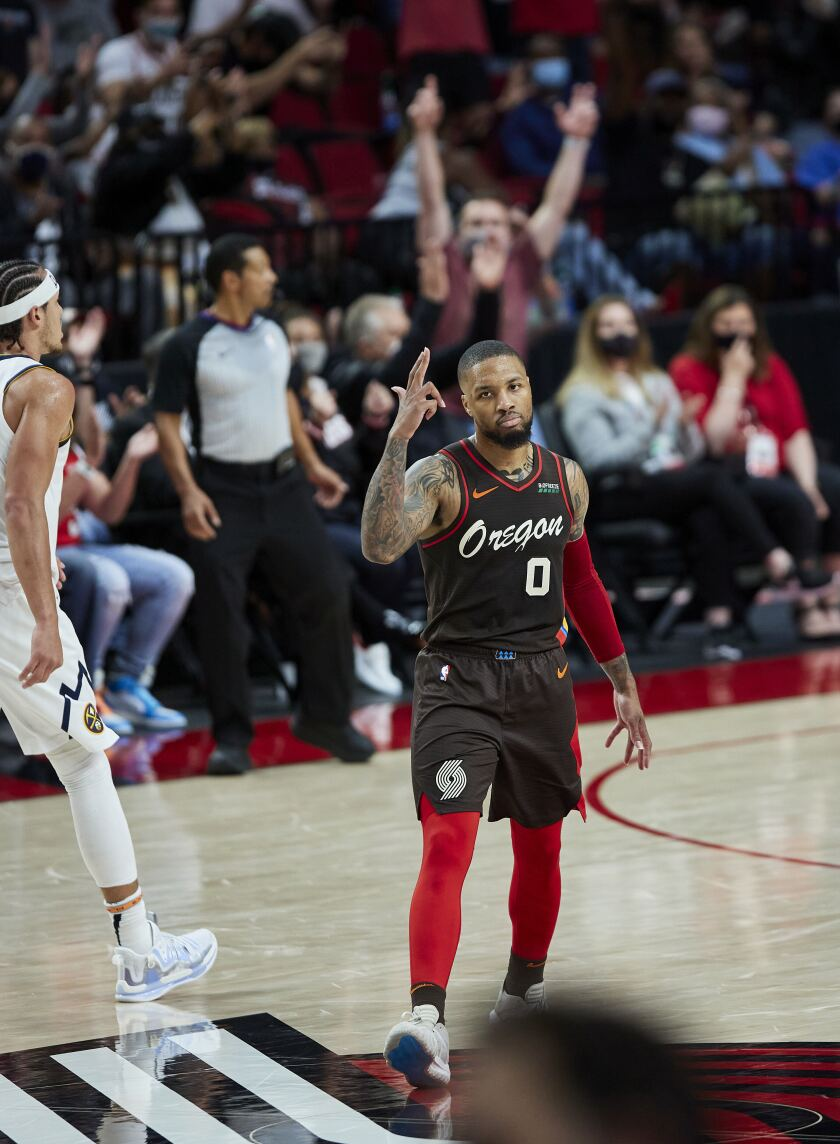 Portland Trail Blazers guard Damian Lillard reacts after making a 3-point basket against the Denver Nuggets during the first half of Game 6 of an NBA basketball first-round playoff series Thursday, June 3, 2021, in Portland, Ore. (AP Photo/Craig Mitchelldyer)