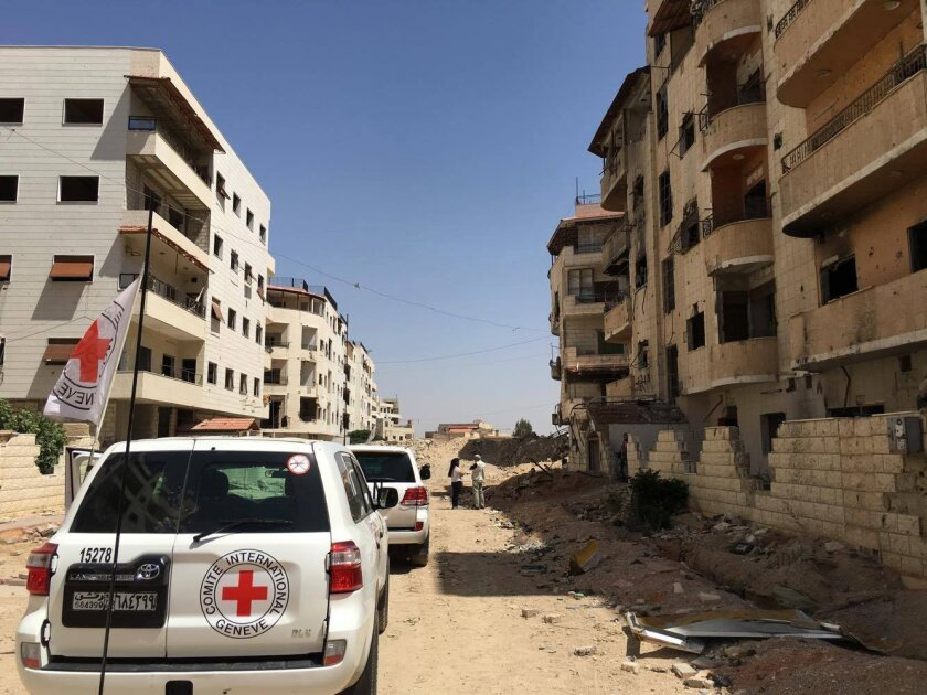 This image released by the International Committee for the Red Cross shows the first humanitarian aid convoy in Daraya, Syria on Wednesday, June 1, 2016. A besieged suburb of Syria's capital received humanitarian aid Wednesday for the first time since 2012, as the United Nations. The International