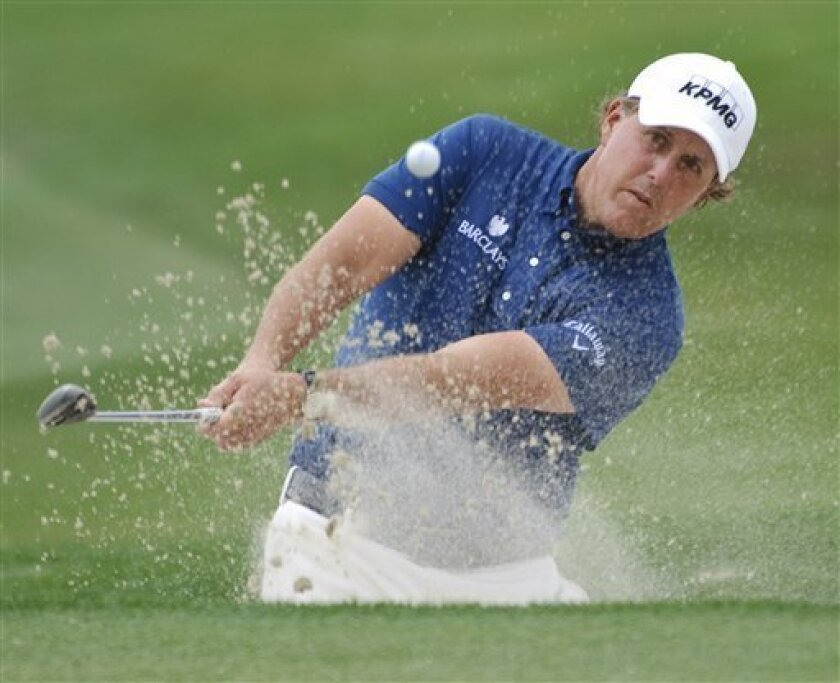 Phil Mickelson hits out of a bunker on the eighth hole during the final round of the Houston Open PGA Tour golf tournament on Sunday, April 3, 2011, in Humble, Texas. (AP Photo/Dave Einsel)