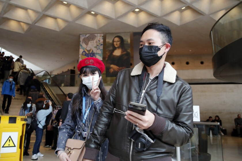 Masked tourists visit the Louvre in Paris.