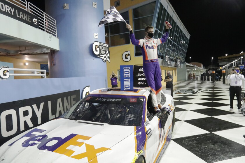 Denny Hamlin celebrates while standing on his car after winning a NASCAR Cup race at Homestead-Miami Speedway.