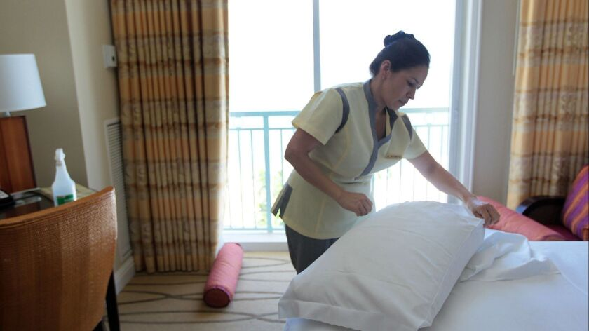 "A housekeeper at a hotel in Miami prepares a room for a new occupant in 2010. A coalition of hotel operators has announced plans to equip hotel workers with ""panic buttons."""