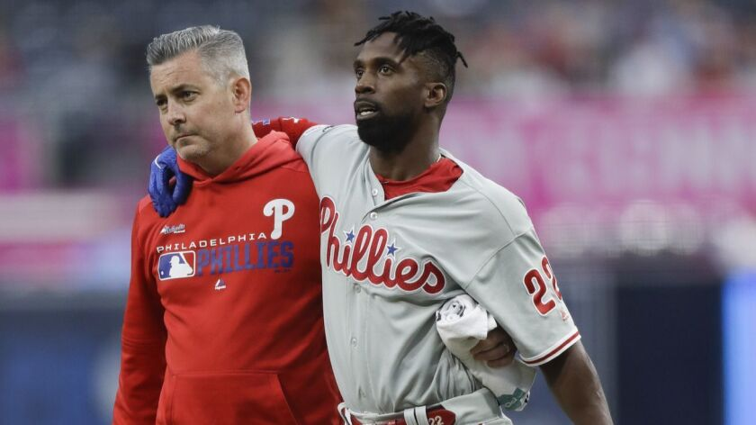 Philadelphia Phillies' Andrew McCutchen, center, is helped by a trainer after being injured trying t