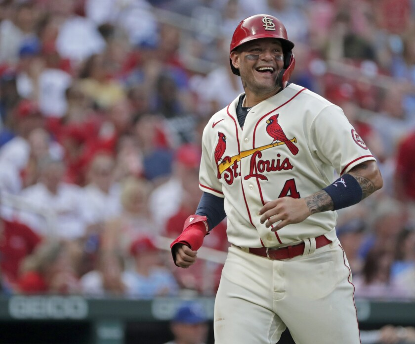 St. Louis Cardinals catcher Yadier Molina smiles while looking toward Kansas City Royals catcher Salvador Perez as Molina heads back to the dugout between the first and second innings of a baseball game Saturday, Aug. 7, 2021, in St. Louis. (AP Photo/Tom Gannam)