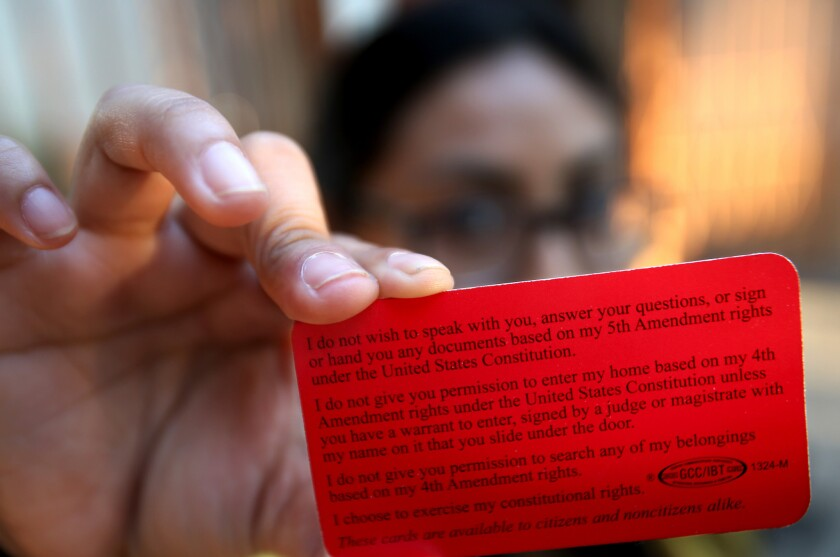 A DACA recipient who asked not to be identified holds up a red card that briefly outlines legal righ