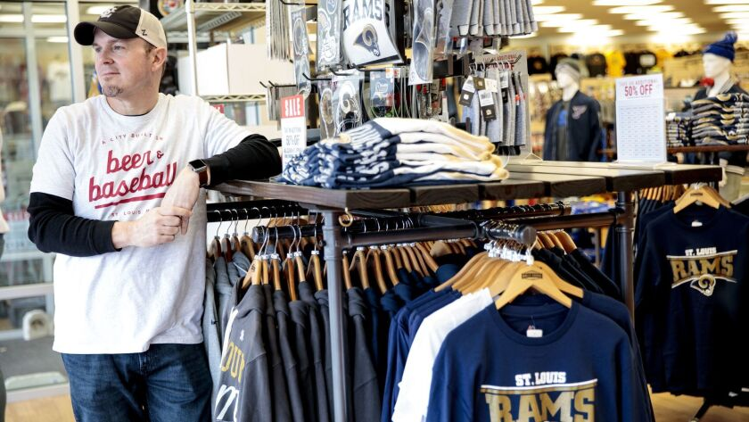 Matt Meier, store manager at Rally House in St. Peters, Mo., stands next to discounted St. Louis Rams merchandise. Many Rams fans left behind in St. Louis will not be cheering for the team when it takes on the Patriots in the Super Bowl.