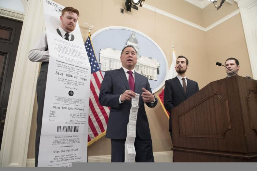 Wil Pond, left, wears a life-sized paper receipt next to Assemblyman Phil Ting, D-San Francisco, to promote a new bill that would eliminate paper receipts all over California.
