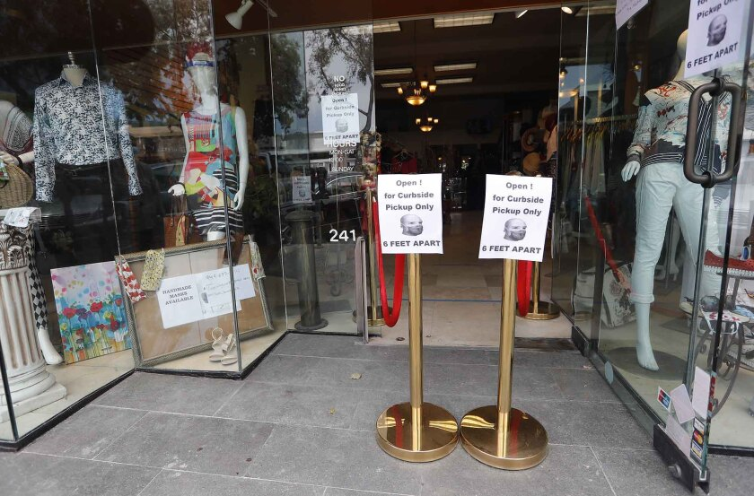 Signs at Laguna Beach's Violet Boutique are a reminder that some low-risk retailers were able to open for curbside pickups as part of the second phase of reopening California.