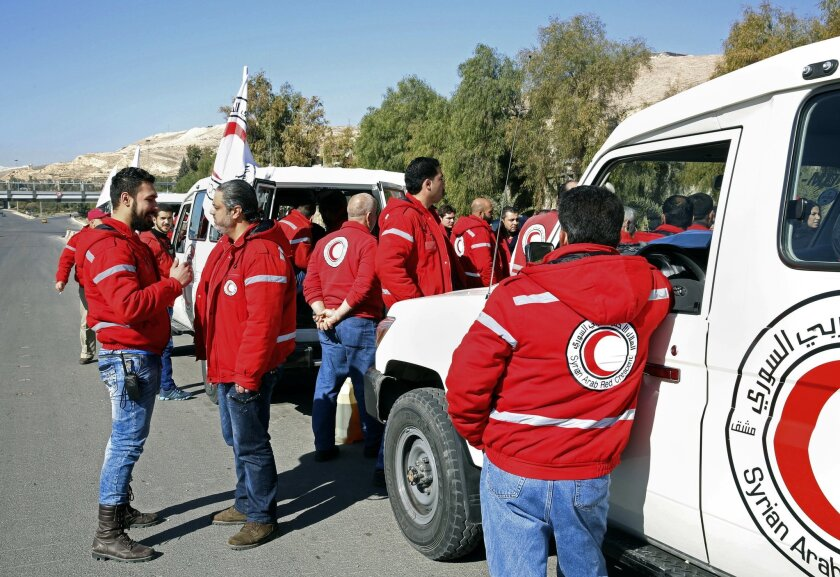 Staff from the Syrian Arab Red Crescent get ready to accompany a convoy of humanitarian aid as it waits in front of the United Nations Relief and Works Agency (UNRWA) offices before making their way into the government besieged rebel-held towns of Madaya, al-Zabadani and al-Moadhamiya in the Damasc
