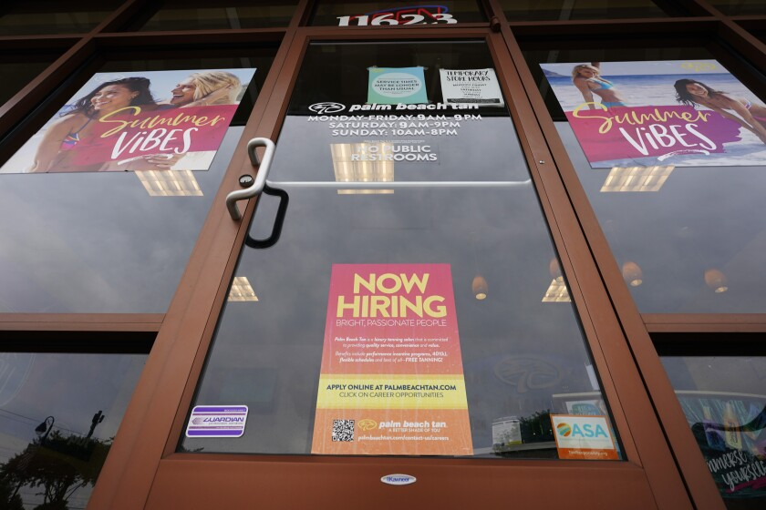 """A """"Now Hiring"""" sign on a door."""