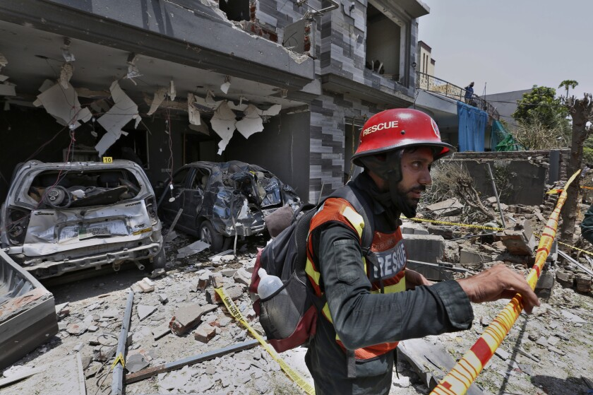 FILE - In this June 23, 2021 file photo, a rescue worker examines the site of explosion in Lahore, Pakistan. In a news conference Sunday, July 4, 2021, in Islamabad, Moeed Yousuf, Pakistan's national security advisor, accused India of orchestrating teh June 23 deadly car bombing in the eastern city of Lahore, saying that an investigation has shown it was organized by an unnamed Indian intelligence operative. (AP Photo/K.M. Chaudary, File)