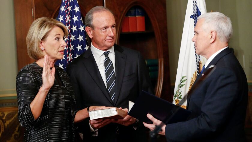 Vice President Mike Pence, right, swears in Education Secretary Betsy DeVos. They are are joined by DeVos' husband Dick DeVos.