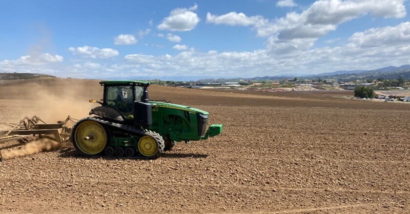 A tractor prepares a field for a spring crop last month along Wilshire Road in South Morro Hills.