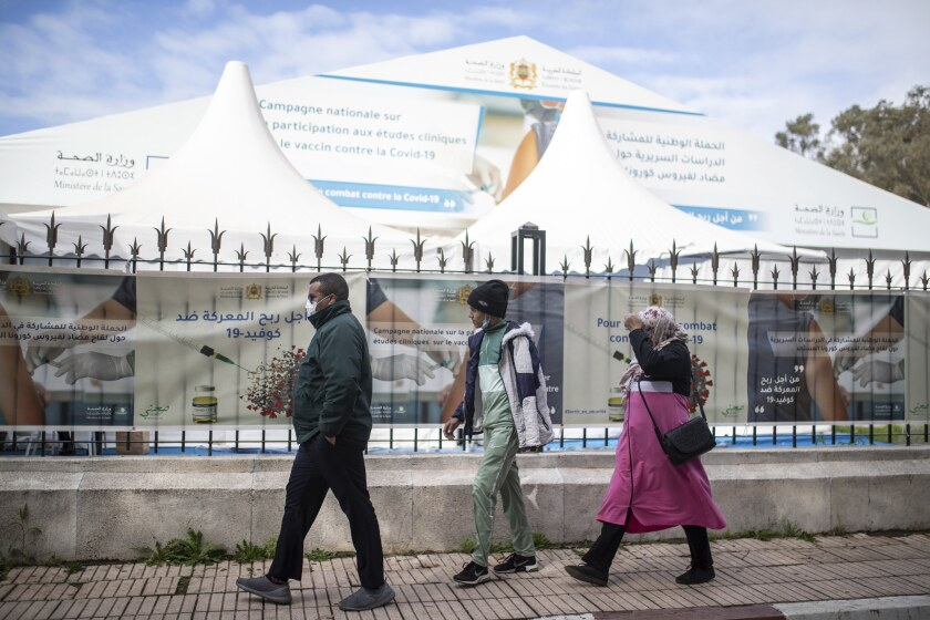 People wearing face masks to prevent the spread of coronavirus walks past a bivouac where clinical trials for covid-19 vaccines are conducted, in Rabat, Morocco, Monday, Dec. 7, 2020. (AP Photo/Mosa'ab Elshamy)