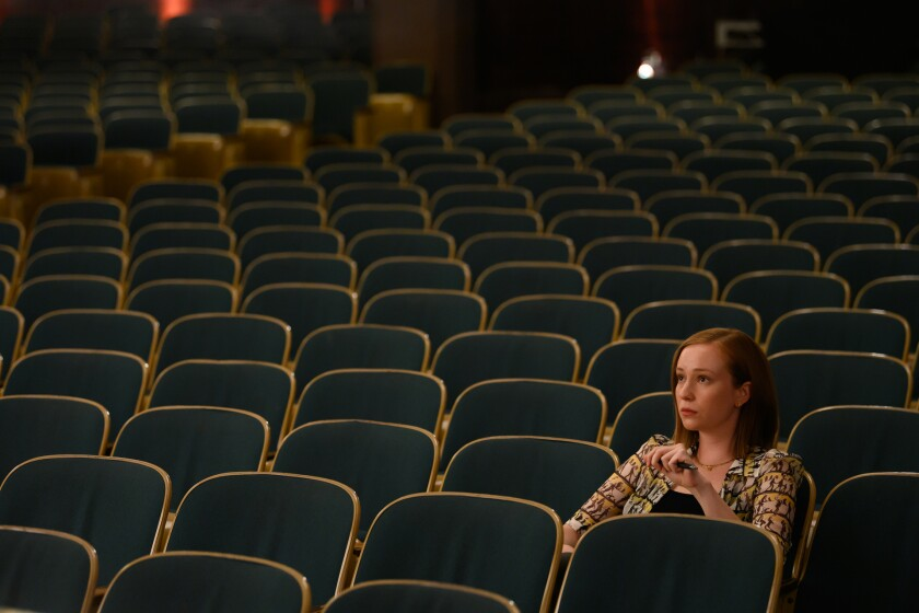 A woman sits in a seat in an empty auditorium.