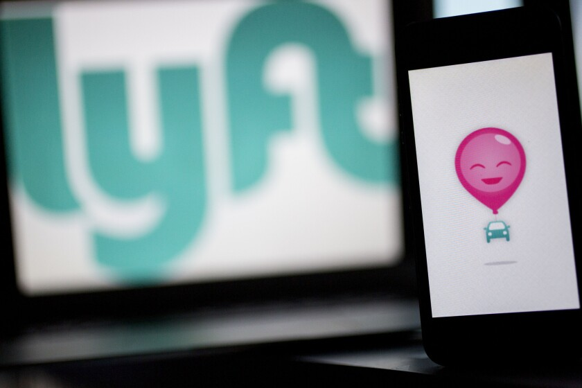 The Lyft Inc. logo and application are displayed on an Apple Inc. iPhone 5s and MacBook Air for an arranged photograph. Lyft is one of the ridesharing services at the heart of a legislative and regulatory battle in Sacramento.