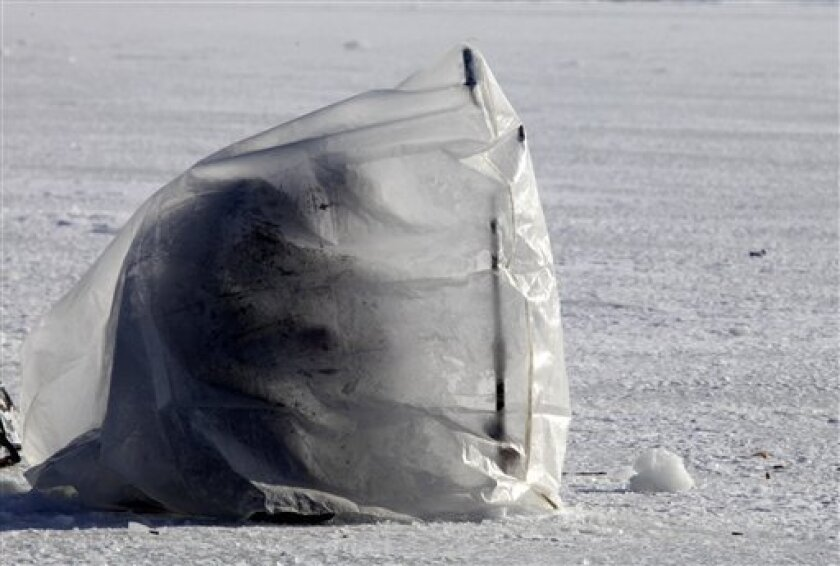 A Ukrainian man, covered with plastic sheeting forming a tent for protection from the wind and cold, fishes through an ice hole on the Dnipro river outside Cherkasy, central Ukraine. Wednesday, Feb. 1, 2012. The death toll from a severe cold spell in Eastern Europe rose to 71 Wednesday, most of them homeless people. Temperatures dropped to minus 30 C (minus 22 F) in some regions, causing power outages and traffic chaos and prompting authorities to close schools and nurseries. (AP Photo/Efrem Lukatsky)