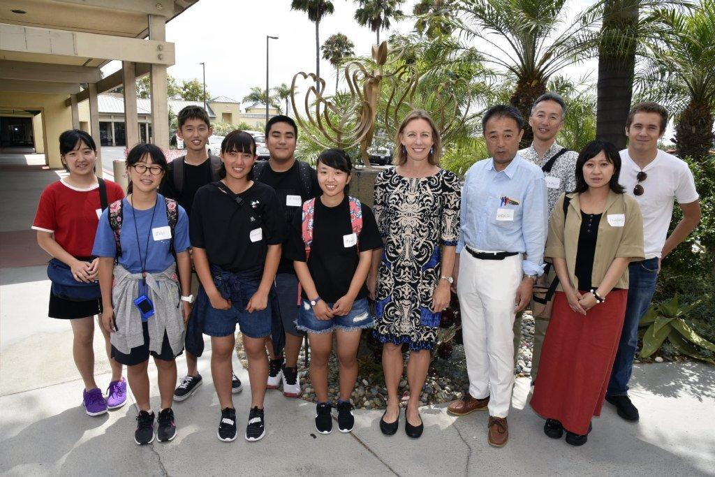 """Mayor Catherine Blakespear (center) is joined by six exchange students from Encinitas sister city Amakusa, Japan (at left), Department of Education delegates Tadashi Nagomoto and Keishi Idenaga, Amakusa teacher Naomi Furuta, and a previous Encinitas exchange student/current student host, at City Hall by the """"Three Dove Monument,"""" a sculpture received as part of a previous Sister City program gift exchange."""