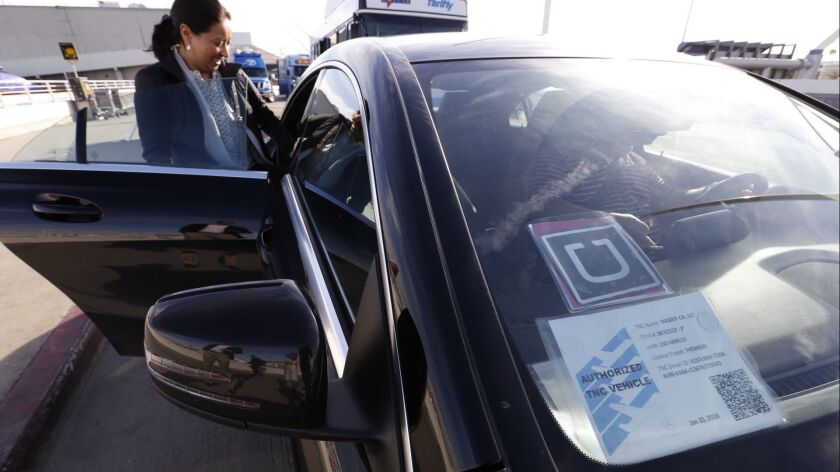 Ann Marie Bingo chats with Uber driver Mike Miller as UberX began making passenger pickups at Los Angeles International Airport in 2016, joining competing service Lyft.