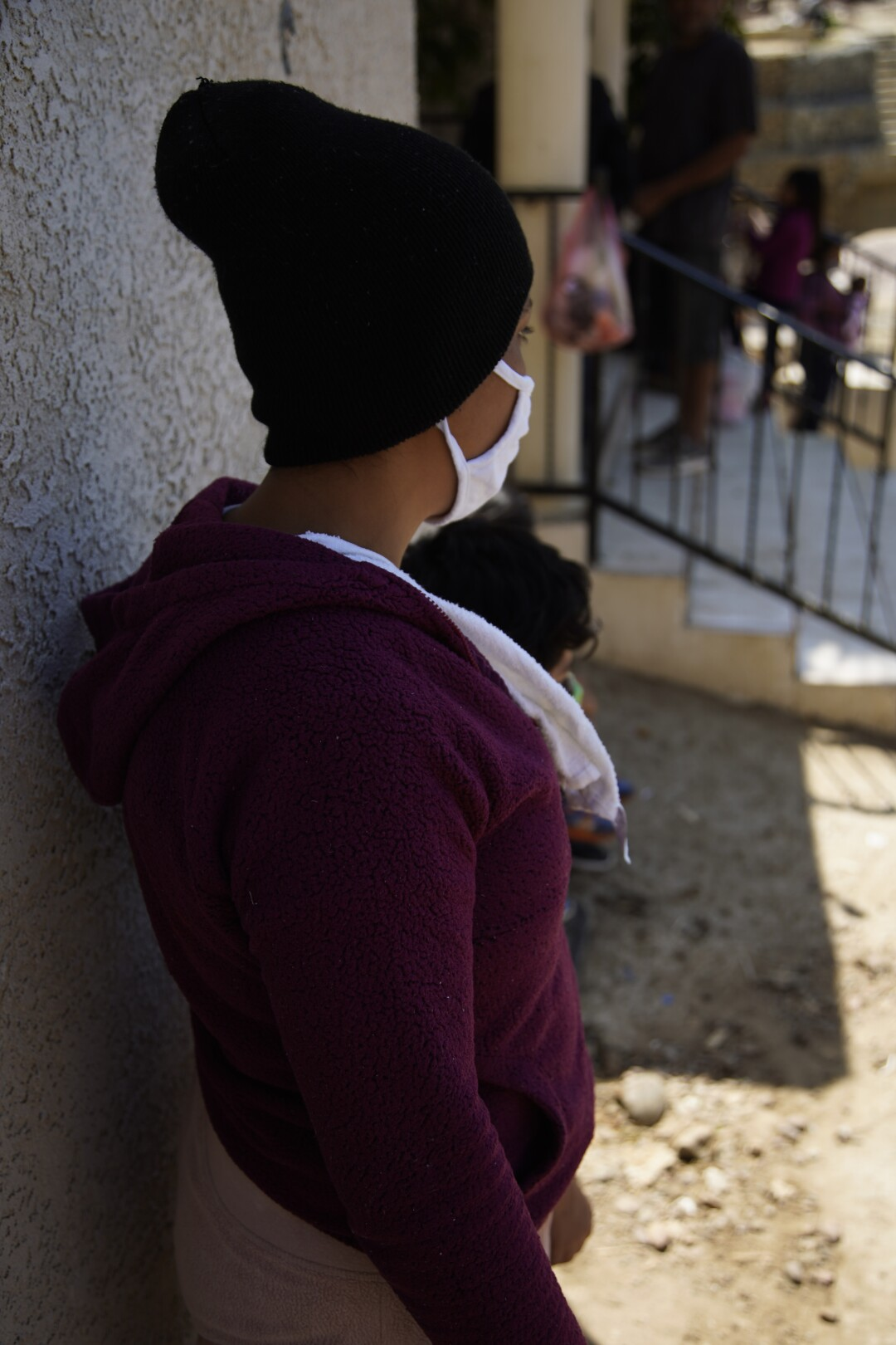 A migrant in Tijuana turns her face away from the camera to avoid being identified