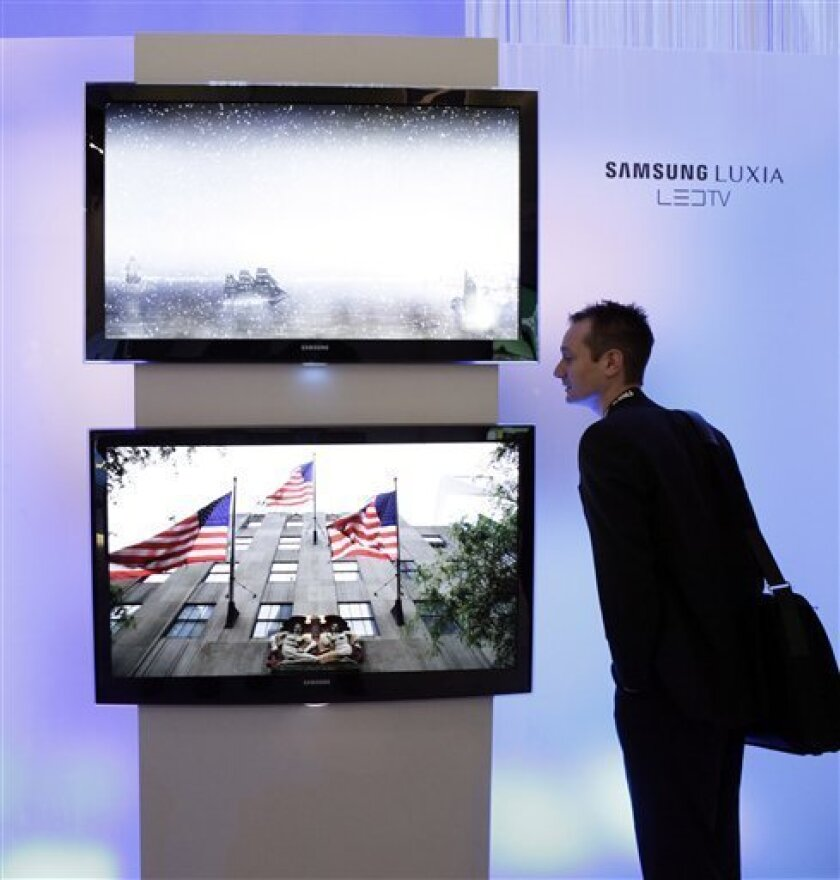 Andy Ellis, of England, looks at Samsung Luxia LED TVs at the International Consumer Electronics Show(CES) in Las Vegas, Saturday, Jan. 10, 2009. (AP Photo/Jae C. Hong)
