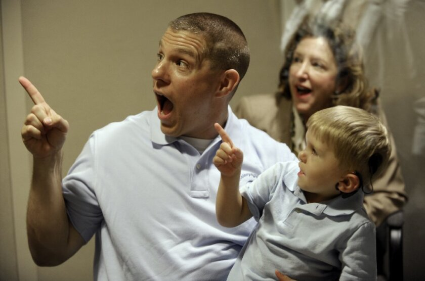 Len Clamp of Charlotte, N.C., reacts with his son Grayson, 3, to hearing and seeing an electronic stuffed animal. Three researchers who were instrumental in developing cochlear implants that could help the profoundly deaf have received the 2013 Lasker Award for clinical research.