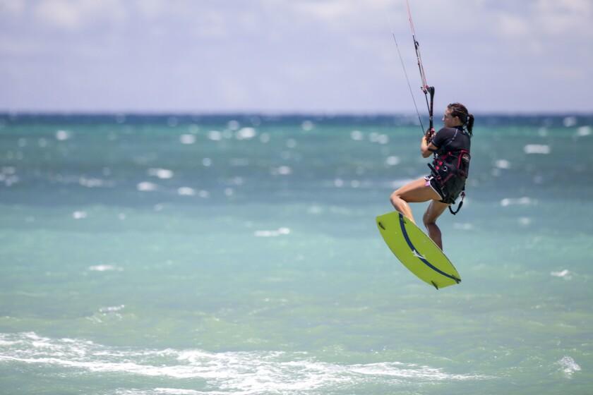 A kite surfer navigates Maui's north shore at the Kiteboarding School of Maui.