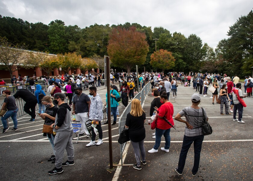 Hundreds of people wearing masks wait in line in a parking lot for early voting in Marietta, Ga.