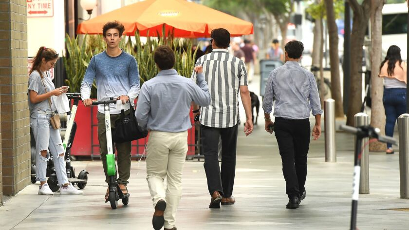 A Lime rider illegally rides a scooter on a sidewalk in Santa Monica before receiving a ticket in July 2018. Students at San Jose State no longer will be allowed to ride the electric vehicles on campus after a ban was enacted on Monday.