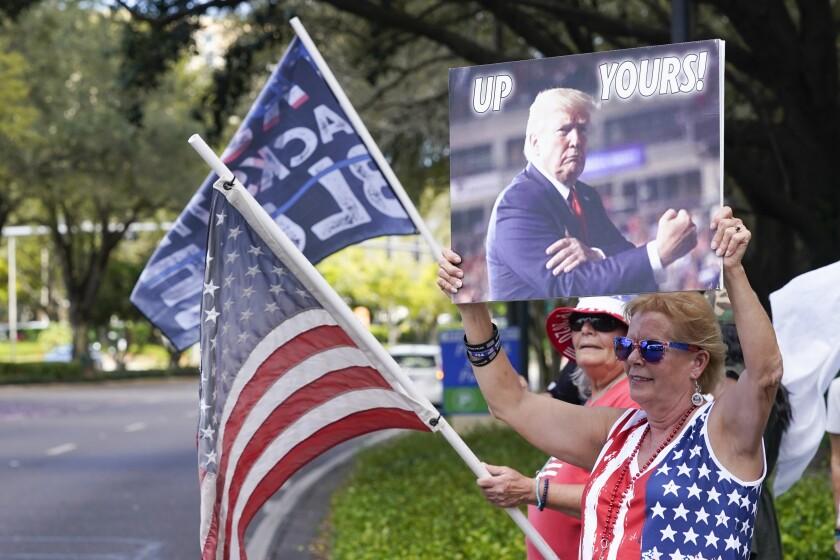 Seguidores de Donald Trump ondean banderas y letreros a los conductores