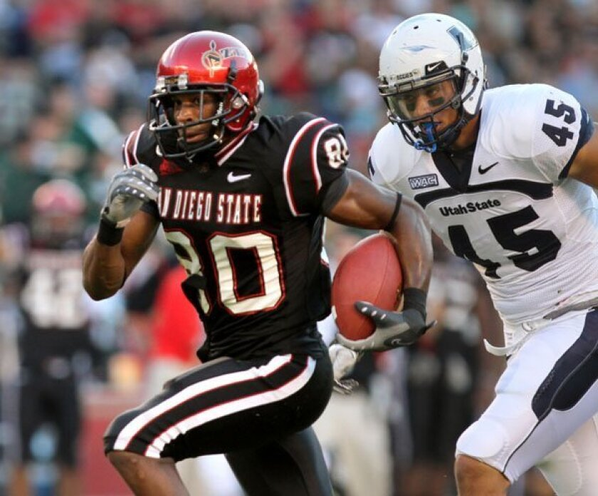 Aztecs receiver Vincent Brown, shown scoring against Utah State and Jerome Barbour.