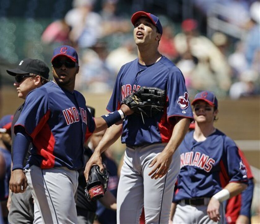 Cleveland Indians starting pitcher Ubaldo Jimenez, center, yells at Colorado Rockies' Troy Tulowitzki as he is held back by first baseman Carlos Santana, left, after Jimenez hit Tulowitzki with a pitch during the first inning of a spring training baseball game on Sunday, April 1, 2012, in Scottsdale, Ariz. (AP Photo/Marcio Jose Sanchez)