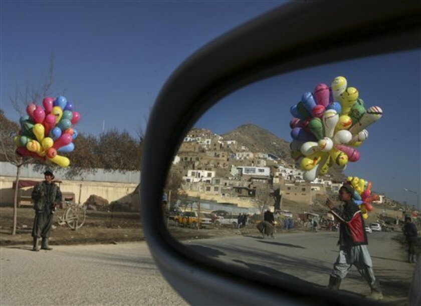 Afghan boys wait for customer to sell balloons in the outskirts of Kabul, Afghanistan, Sunday, Feb. 8, 2009.(AP Photo/Rafiq Maqbool)