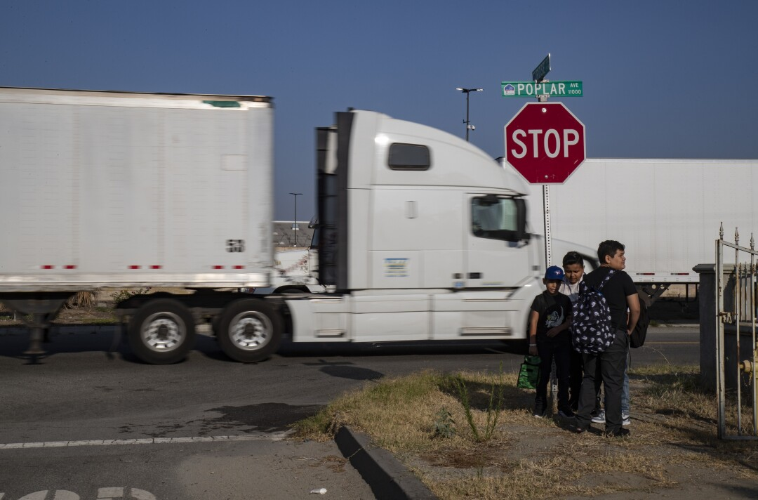 Trucks pass schoolchildren waiting at a bus stop in Fontana.