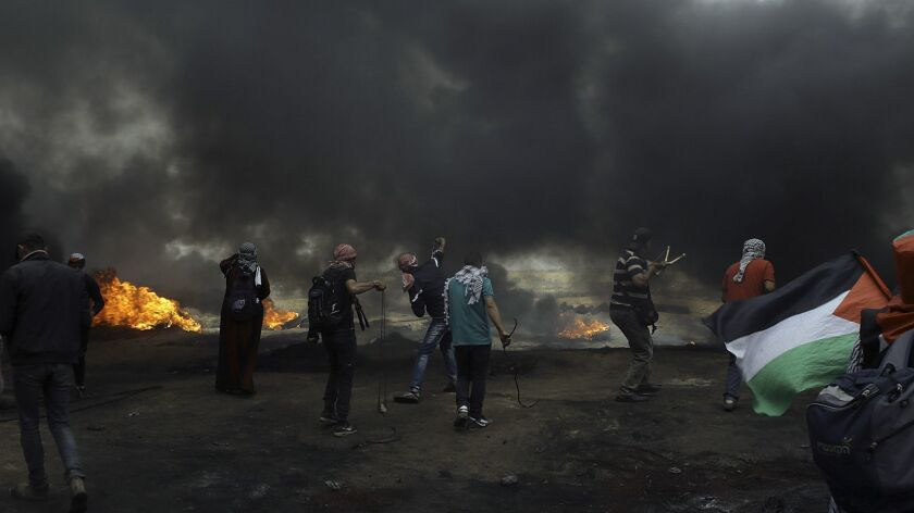 Palestinian protesters in the Gaza Strip hurl stones at Israeli soldiers near the fence amid smoke from burning tires at a May 4, 2018, border demonstration.